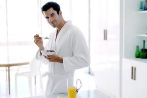 hombre en albornoz desayunando