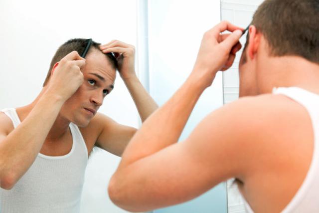 Hombre peinándose ante el espejo