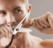 Hombre cortándose la barba con tijeras
